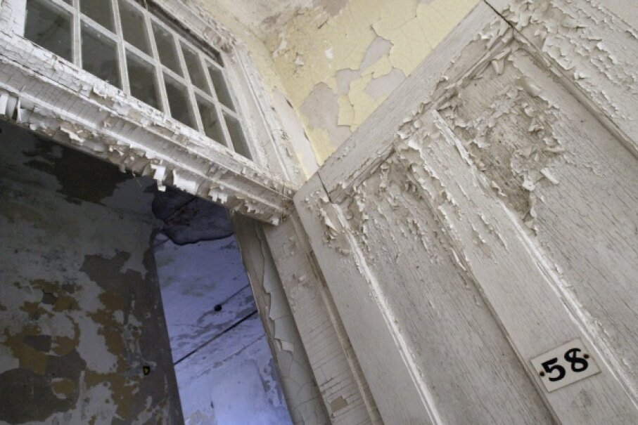 Lead paint peels from the door and walls of patient room number 58 at the Traverse City State Hospital in Michigan. The Victorian Italianate building now houses an upscale restaurant and private and commercial condominiums. © Robert Sciarrino/Star Ledger/Corbis