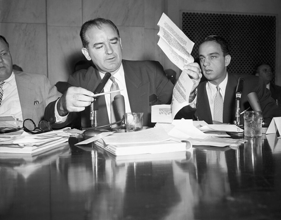 "During a House Un-American Activities Committee hearing, Sen. Joseph McCarthy holds up a letter purportedly written by FBI director J. Edgar Hoover in 1941 warning that a Fort Monmouth employee had a ""direct connection with an espionage agent."" Attorney Roy Cohn sits beside McCarthy. Bettmann/Getty Images"