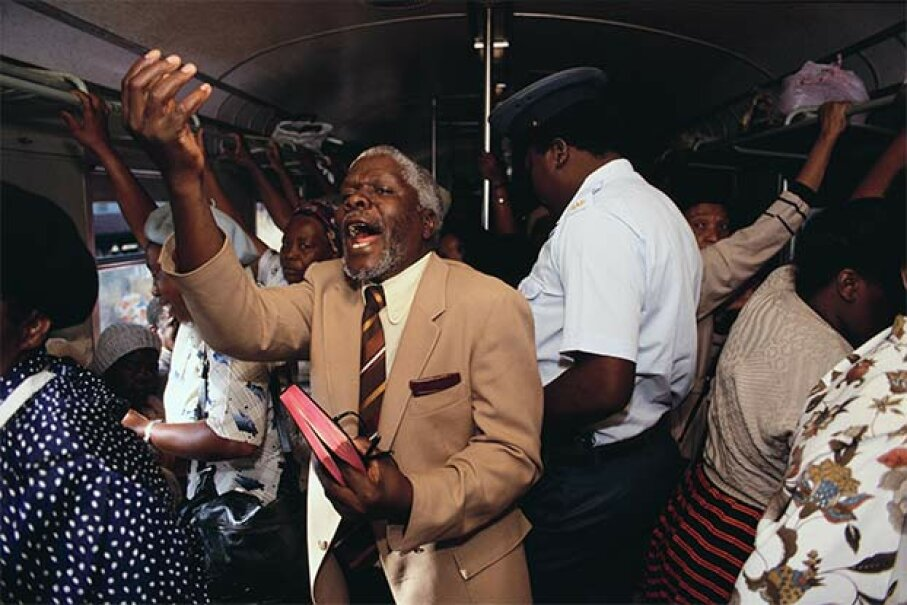 A preacher holds an impromptu service on a train going between Soweto and Johannesburg. © Gideon Mendel/Corbis