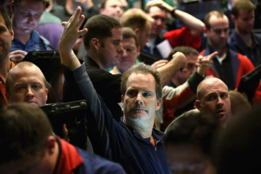 A trader signals an offer at the Chicago Board Options Exchange in December 2012 after the Fed announced it expected to keep a key short-term interest rates at or near zero percent. Scott Olson/Getty Images