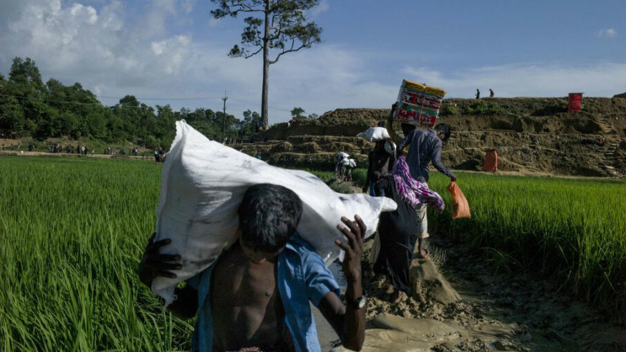 Rohingya Muslim refugees holds bags of goods as they reach Balukhali refugee camp by the field in Bangladesh's Ukhiya district on October 4, 2017.  Thousands now cross the border each day.  FRED DUFOUR/AFP/Getty Images