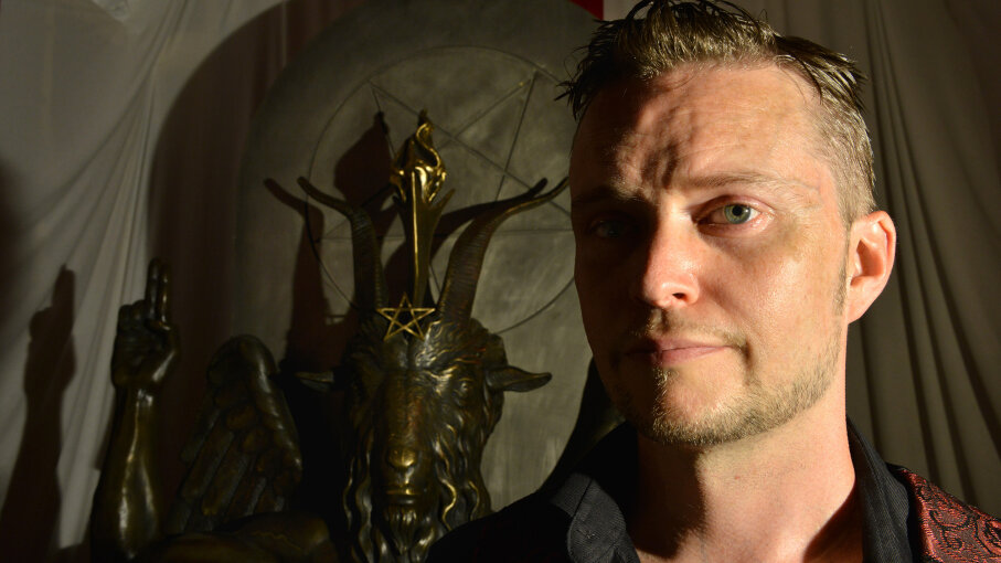 Satanic Temple spokesperson Lucien Greaves stands in front of a statue of Baphomet. The church is known for its outspokenness on social and political issues. The Washington Post/Getty Images