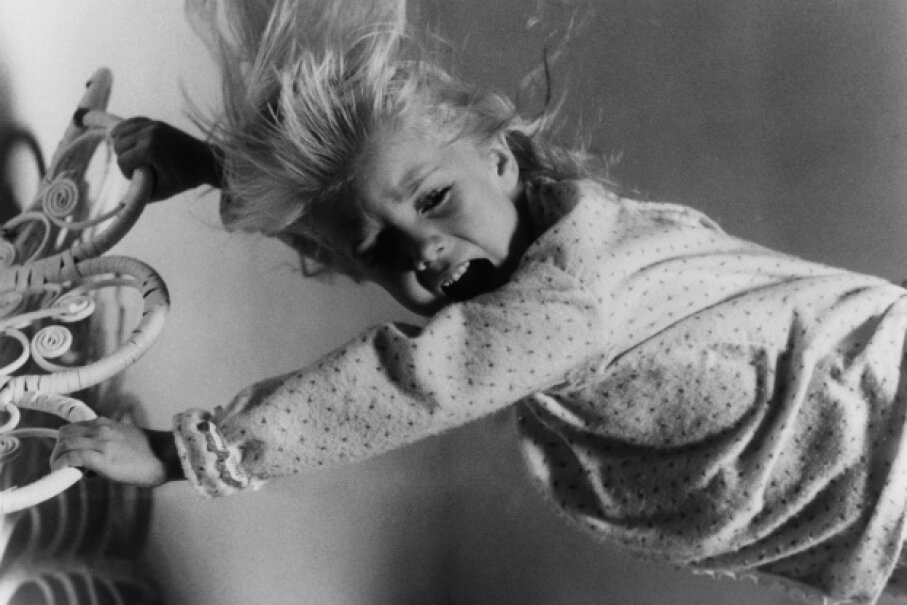 """Carol Anne (played by Heather O'Rourke) tries to prevent the TV people from scooping her up in """"Poltergeist."""" Metro-Goldwyn-Mayer/Getty Images"""