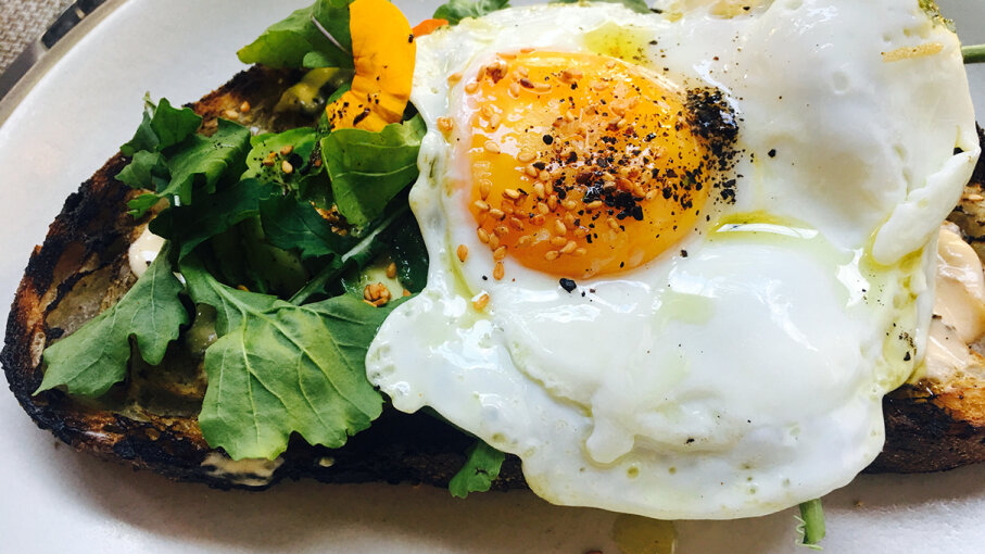 Starting the day off with a small healthy breakfast, like this high protein avocado toast topped with egg, can have many benefits. Westend61/Getty Images