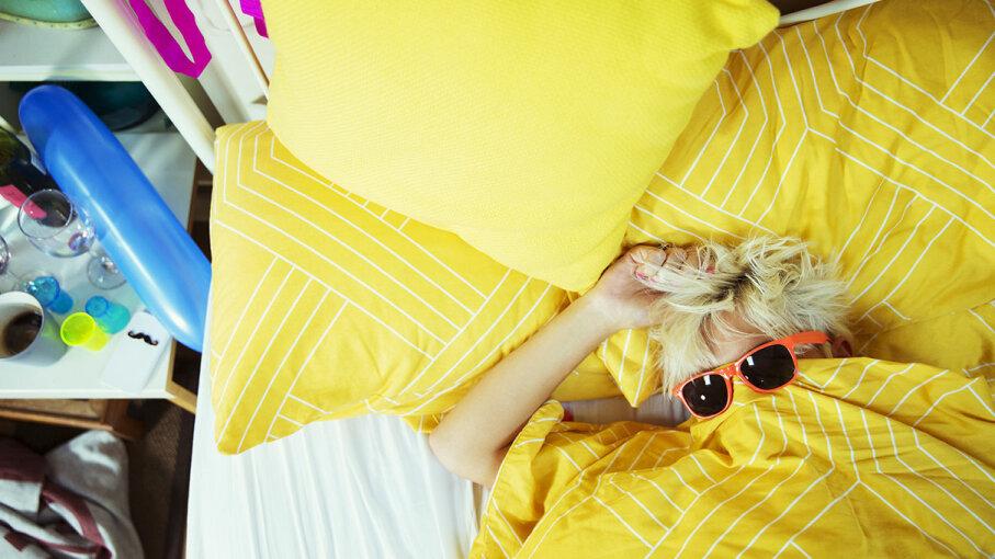 woman lying on yellow comforter, wearing sunglasses