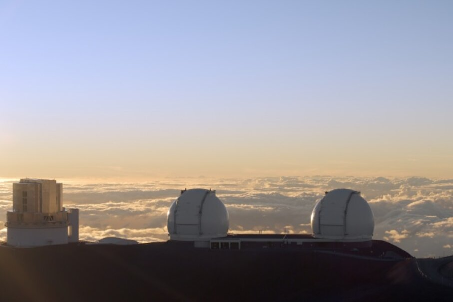 The Subaru Telescope and the Twin Telescopes of the W. M. Keck Observatory peer at their surrounding from their perch above the clouds at Hawaii's Mauna Kea. Someday, we may install a telescope on the moon. © Ed Darack/Science Faction/Corbis