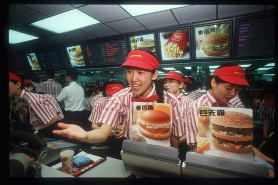 A worker takes an order from a customer in China's first McDonald's restaurant, back in 1992. According to the 'Big Mac Index,' global currency values can be measured by looking at the price of a Big Mac in various countries. Forrest Anderson/Getty Images