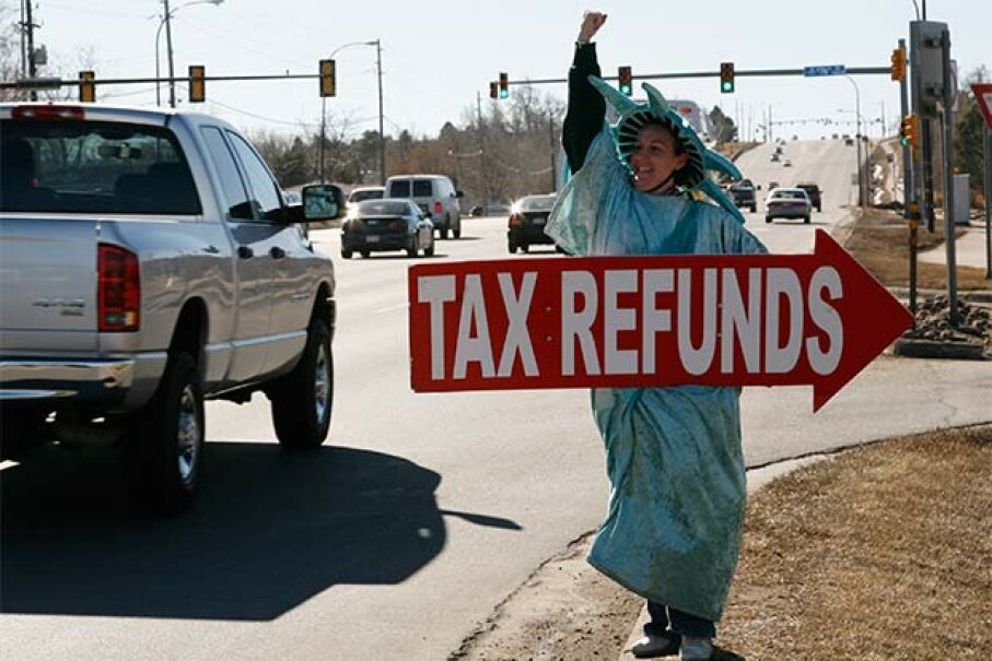 Shannon Philbrick, dressed as the Statue of Liberty, waves a sign at drivers to encourage them to come to Liberty Tax Services to get their taxes done. Most of the tax preparers at places like these are not accountants. © RICK WILKING/Reuters/Corbis