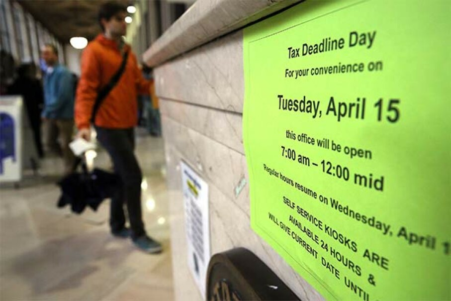A sign states the business hours in the James A. Farley post office in Manhattan, which is staying open until midnight on the last day to file taxes, April 15, 2014. Spencer Platt/Getty Images