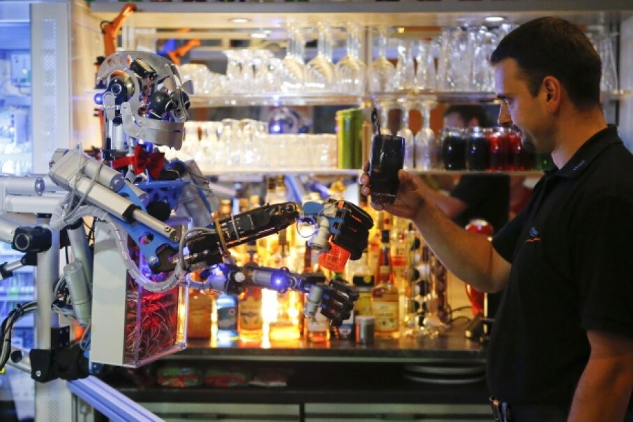 Mechatronics engineer Ben Schaefer interacts with humanoid robot bartender Carl as it prepares a drink at the Robots Bar and Lounge in Germany on July 26, 2013. Developed by Schaefer, Carl also can interact with customers in small conversations. © Fabrizio Bensch/Reuters/Corbis