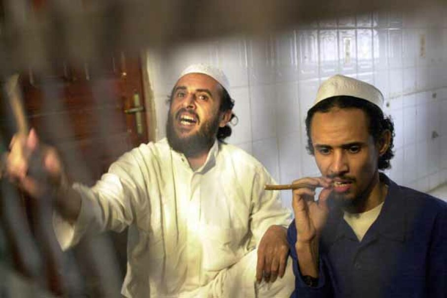 Jamal Mohammed al-Bedawi (L) shouts from behind bars and Fahd al-Quso (R) looks on as they hear the verdict in Yemen at the end of the trial of six militants charged with the October 2000 bombing of the Navy destroyer USS Cole. KHALED FAZAA/AFP/Getty Images