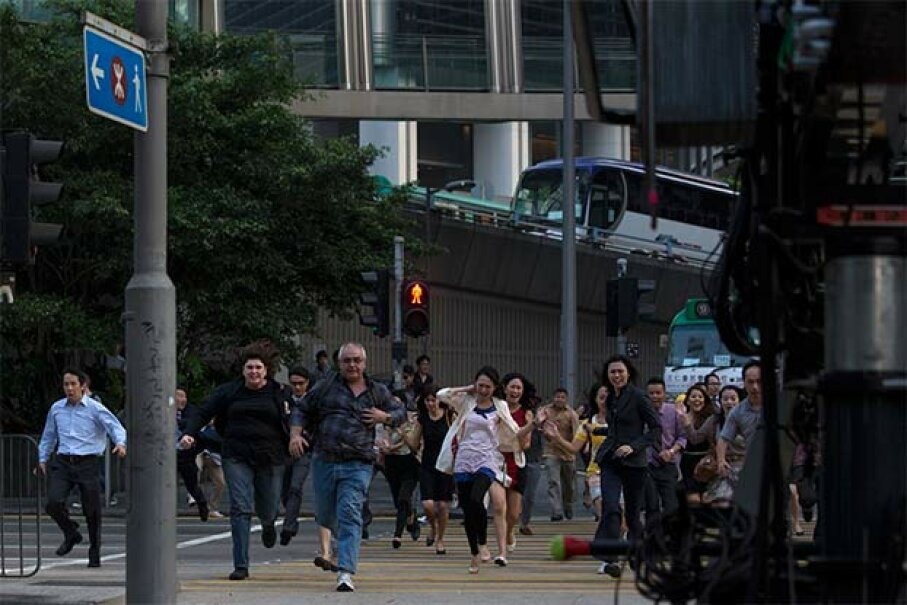 Extras run across the street during the filming of a scene for 'Transformers: Age of Extinction' in Hong Kong's financial Central district in 2013. © TYRONE SIU/Reuters/Corbis