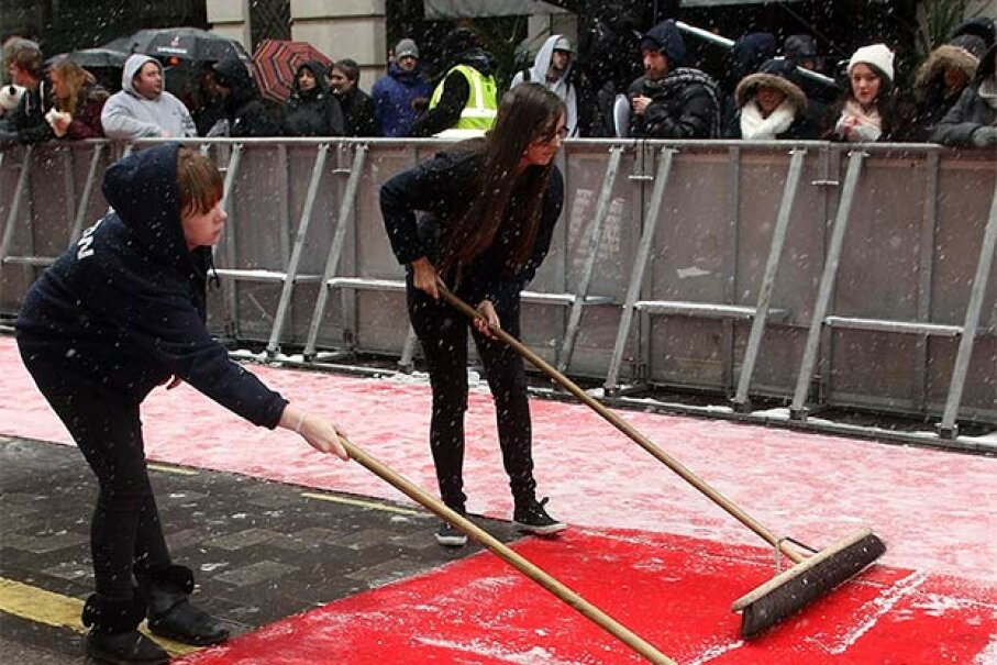 Two production assistants clear snow from the red carpet during arrivals of the London judges for 'Britain's Got Talent' in 2013. Danny Martindale/Getty Images