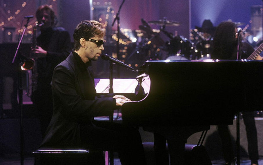 Prince (then known by an unpronounceable symbol) performs on the David Letterman Show in 1996, with the word 'slave' written on his cheek. Alan Singer/CBS via Getty Image