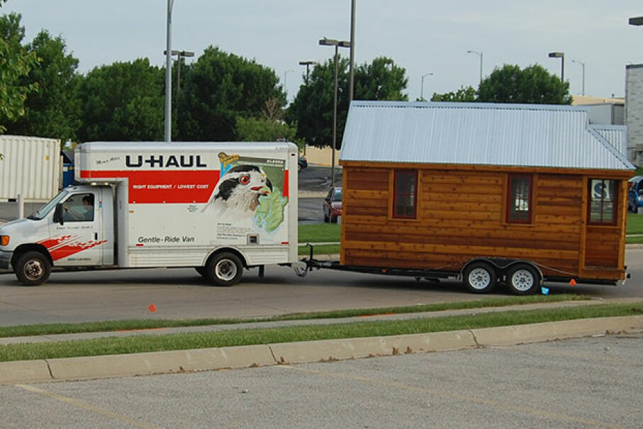 A U-Haul van tows a tiny house to its next destination. Tiny houses don't tow as easily as RVs. Matt Harriger Used Under Creative Commons CC By -SA 2.0 License