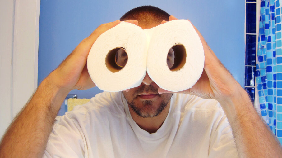 Man holding toilet paper as binoculars