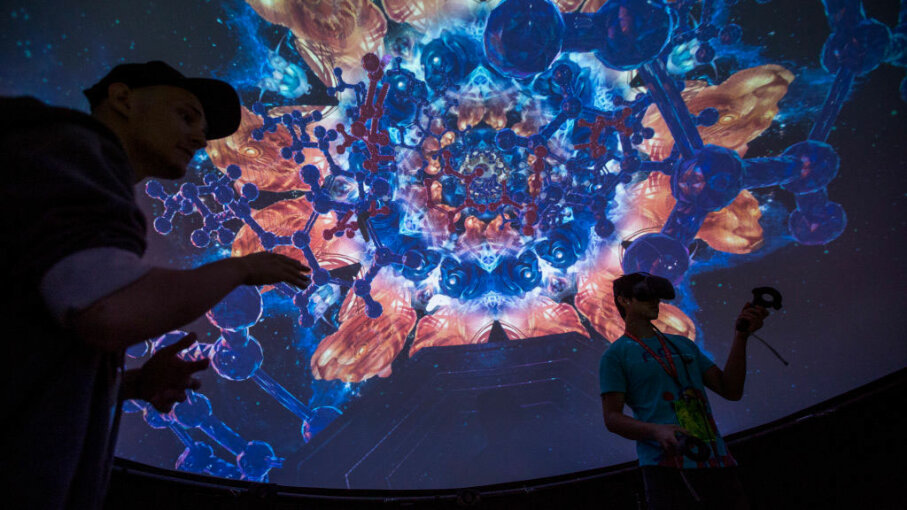 An exhibitor helps a man try out a virtual reality game inside a Fulldome.pro 360-degree projection dome on opening day of the Electronic Entertainment Expo (E3) at the Los Angeles Convention Center on June 13, 2017. Los Angeles was No. 6 on the top cities for gamers list. David McNew/Getty Images
