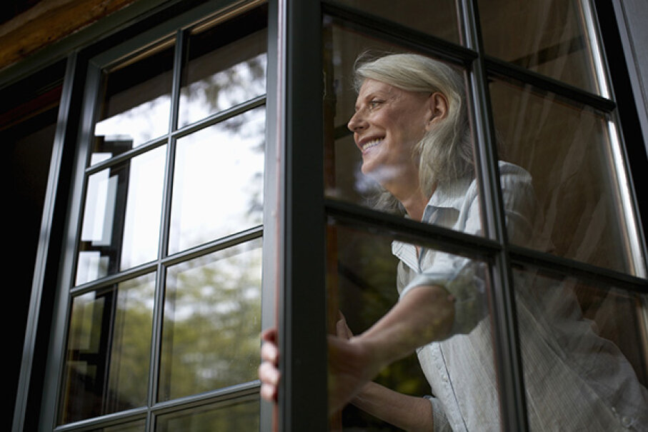 She wouldn't be smiling if she knew how unsafe opening windows during a tornado can be. Kim Carson/Photodisc/Thinkstock