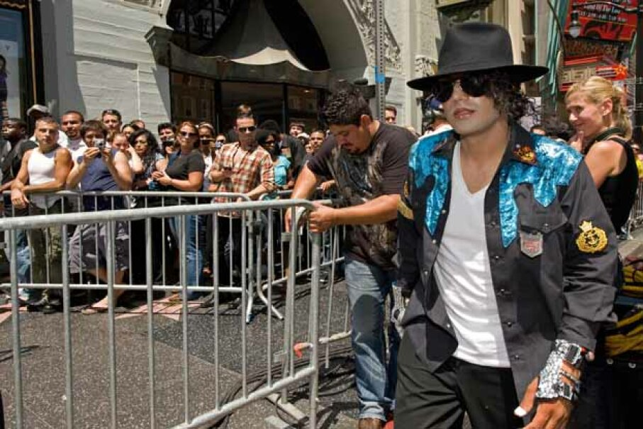 A Michael Jackson impersonator walks before crowds of fans waiting to pay their respects at Michael Jackson's star on the Hollywood Walk of Fame on Hollywood Blvd. PAUL J. RICHARDS/AFP/Getty Images