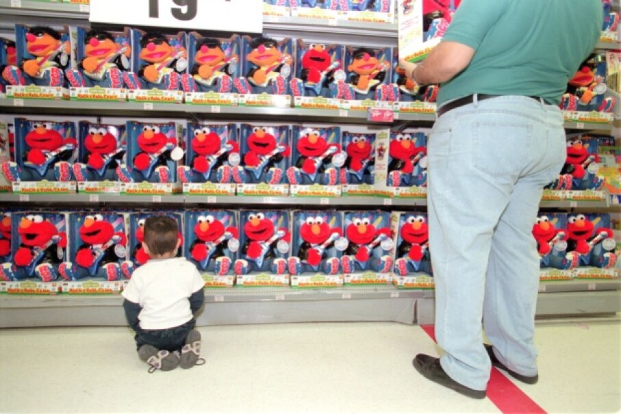 Andrew Rosas, 2, looks at Rock and Roll Elmo and Ernie while sitting on the floor of a store. Michael Stuparyk/Toronto Star via Getty Images