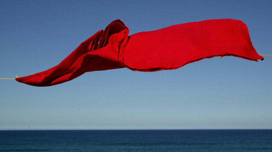 red sheet on clothesline by the ocean
