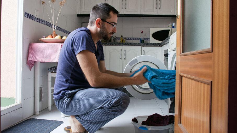 man folding laundry