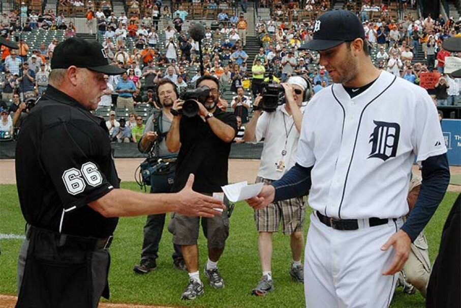 Major League umpire Jim Joyce receives the lineup card from Detroit Tigers pitcher Armando Galarraga before the start of a game against the Cleveland Indians; earlier, Joyce apologized to Galarraga for the bad call which cost him a perfect game. Mark Cunningham/MLB Photos via Getty Images