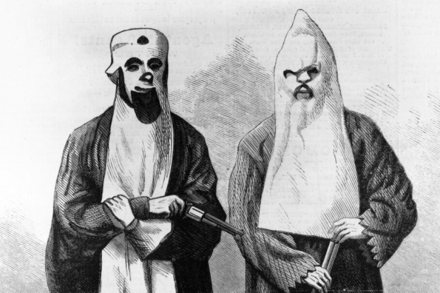 This 1866 wood engraving depicts two members of the Ku Klux Klan. The white sheet and hood were supposed to represent the ghosts of Confederate soldiers risen from the dead to seek revenge. MPI/Getty Images
