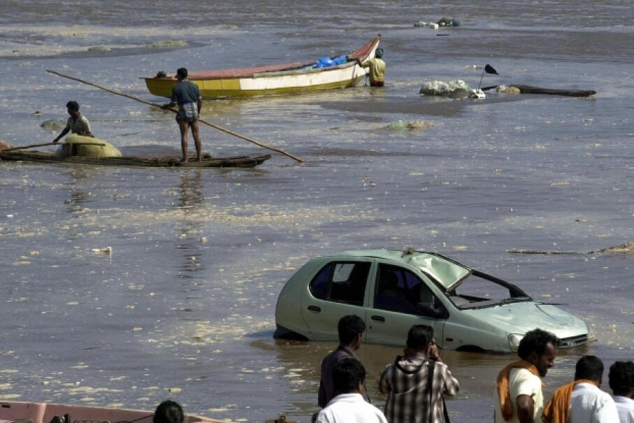 People gaze out at the floodwaters in Madras, India, after the December 2004 tsunami. STR/AFP/Getty Images